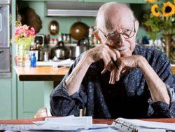 Un vieil homme assis à une table devant un classeur.