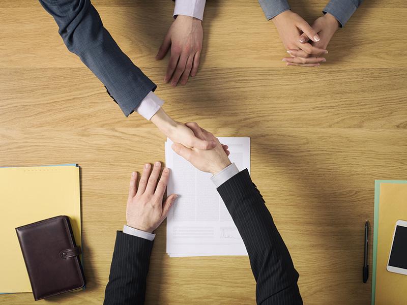 Poignée de main entre un conseiller et ses clients.