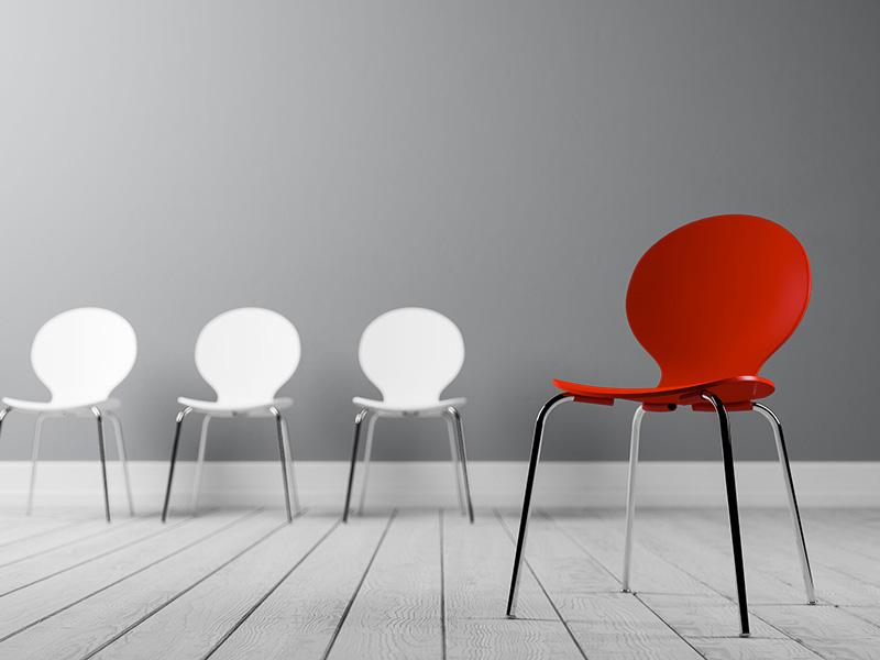 Trois chaises blanches et une chaise rouge.