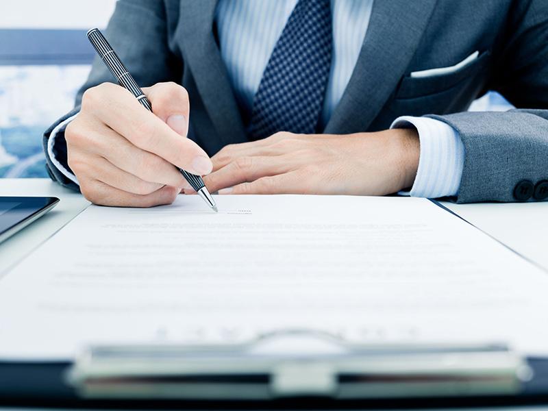 Homme d'affaires en train d'apposer sa signature sur un document.
