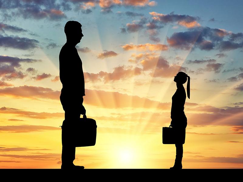 Un homme géant et une femme minuscule debout devant un coucher de soleil.