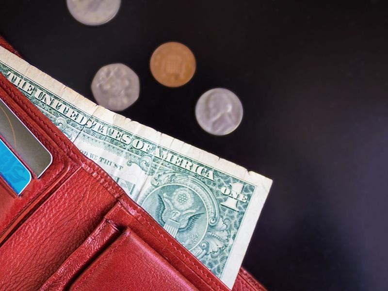 Portefeuille contenant un billet de banque américain, et pièces de monnaie.