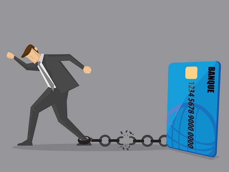 Homme d'affaires portant un boulet à son pied, rattaché à une carte de crédit géante.