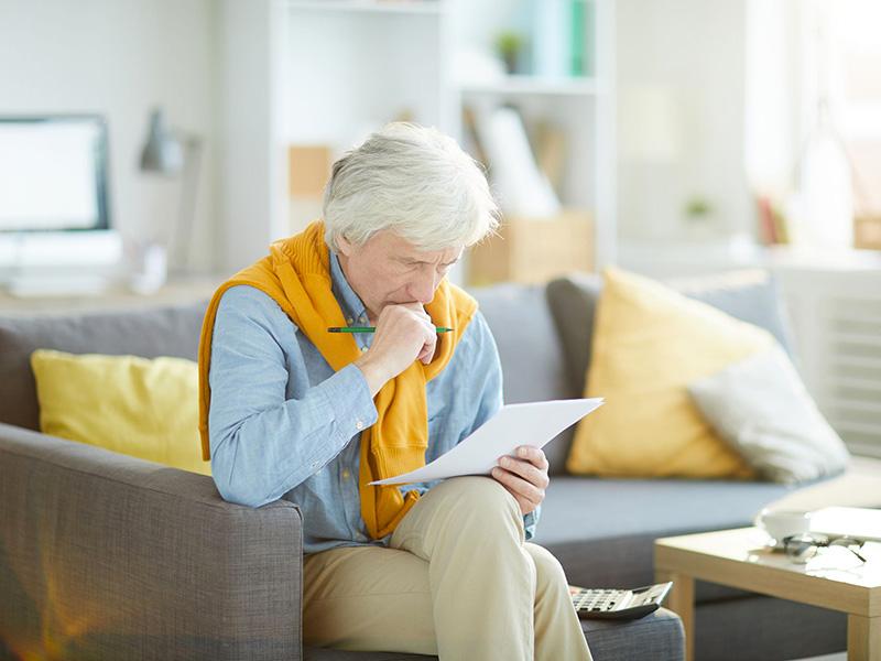 Homme retraité inquiet en consultant un document.