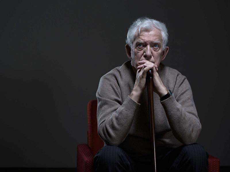 Homme âgé, pensif, assis sur une chaise dans la pénombre.