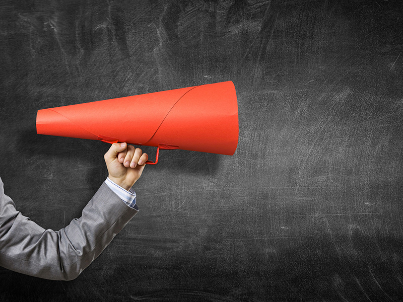 Bras d'un homme d'affaires tenant un porte-voix rouge.
