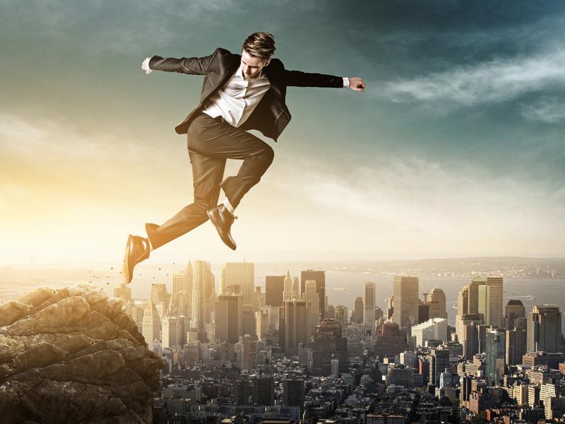 Un homme d'affaires sautant d'une montagne, la ville en contrebas.