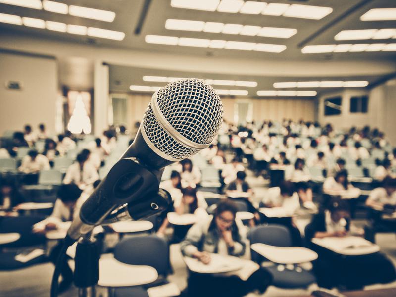 Micro à l'avant-plan avec auditorium rempli d'élèves à l'arrière-plan.