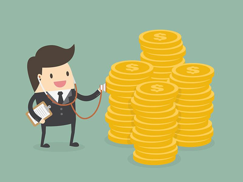 Un homme d'affaires muni d'un stéthoscope évaluant un tas de pièces d'or.