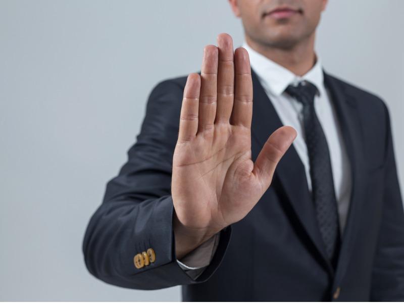 Un homme d'affaire, la main en avant, faisant le signe de stop.
