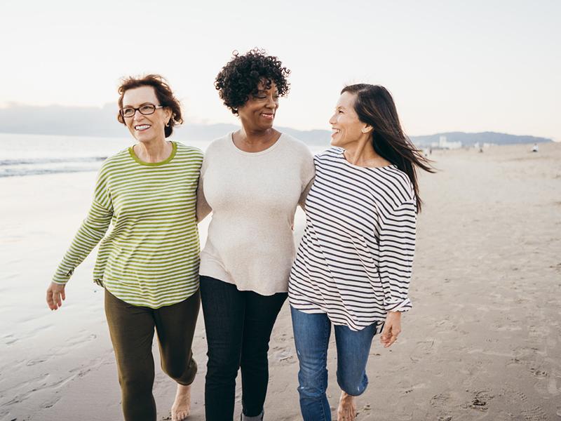Trois femmes font une promenade sur la plage.