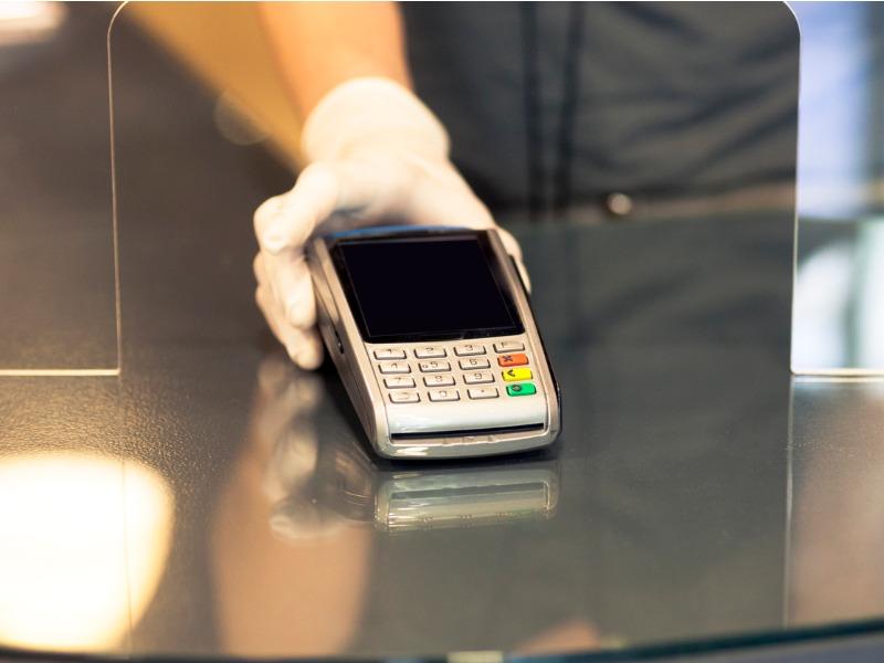 Main gantée qui tend un appareil de paiement par l'ouverture d'une vitre de protection.