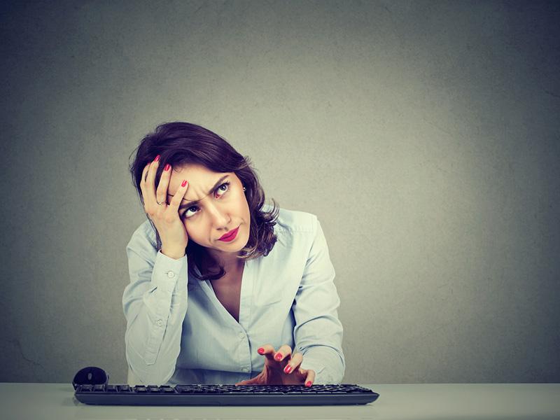 Femme désespérée devant le clavier de son ordinateur.
