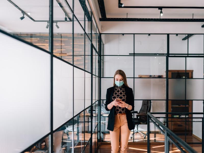 Femme portant un masque en train de regarder son téléphone intelligent dans un bureau.