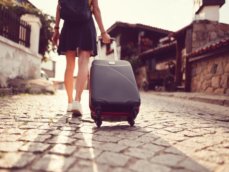 Une femme qui marche dans la rue avec une valise à la main.
