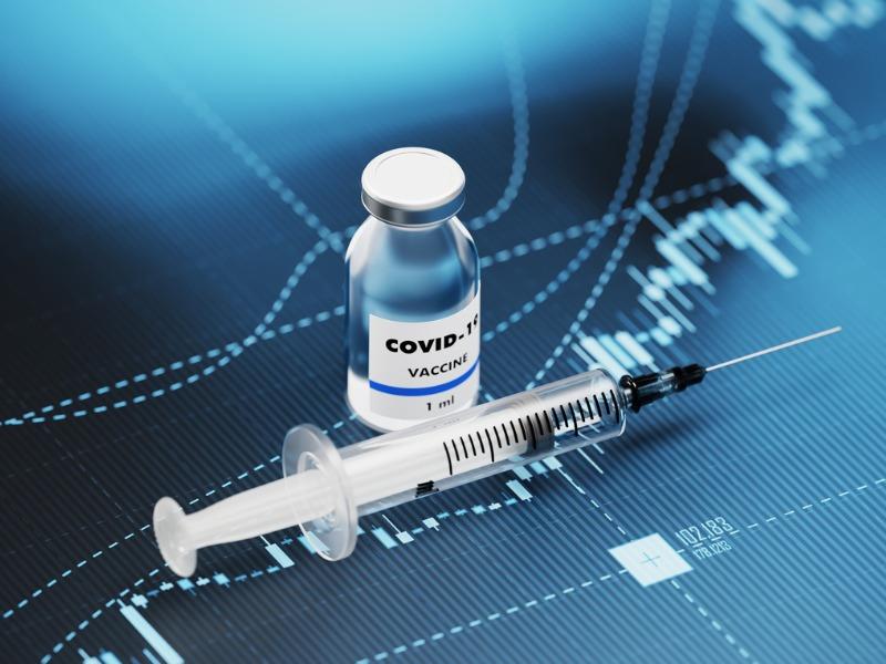 Une aiguille posée à côté du vaccin contre la COVID-19, le tout sur un graphique financier à la hausse.